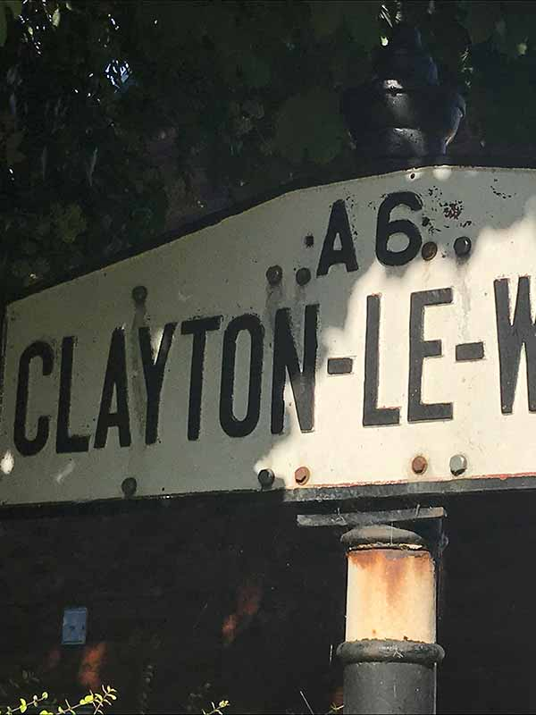 a road sign displaying Clayton-le-Woods